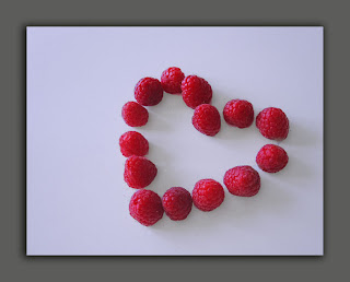 A card of red raspberries in the shape of a heart.