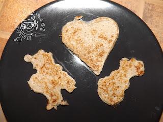 Szöveg: Szív-, mikulás- és hóemberalakú palacsinták. Kép: Szürkés árnyalatú fekete tányéron elhelyezve egy-egy szív, mikulás- és hóemberformájú palacsinta.