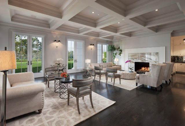 Living room mansion coffered ceiling wood floor marble fireplace mantel white armchairs with nail head trim white sofa French doors