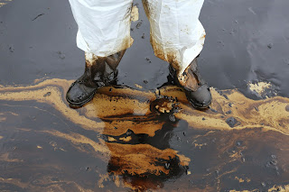 Man in boots stands in an oil spill on the beach