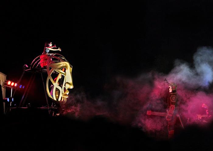 Espectáculo nocturno envolvendo marionetas gigantes comandadas por actores. Ambiente carregado de fumos trespassados por iluminação colorida