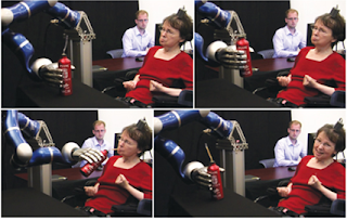 Picture of a Lady using a Robotic Arm to Drink