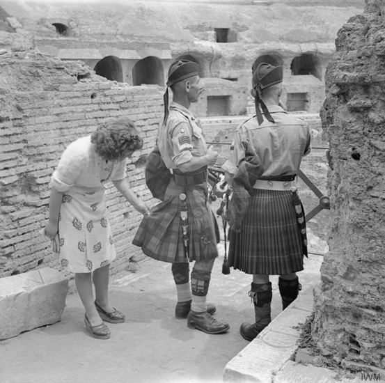 An Italian woman inspects the kilts of two pipers 1944