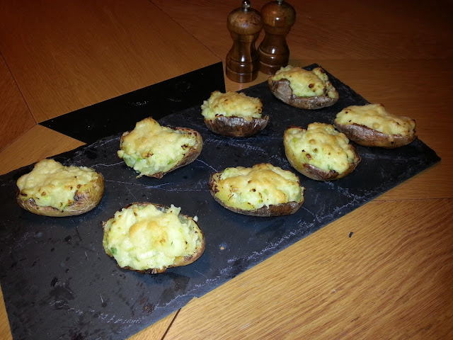 Loaded double baked potato shells on slate.