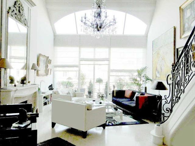 Living room in a Paris apartment with white and black dueling sofas, large mirror and grand staircase