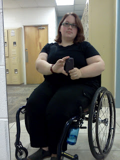 Author sitting in dark blue framed wheelchair with water bottle hanging off a wheel lock, wearing a black fitted tshirt and the black cargo pants mentioned in the paragraph