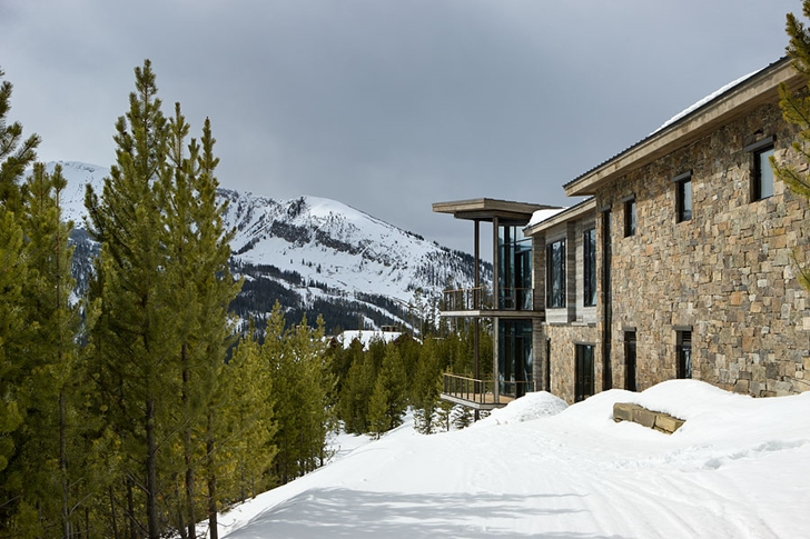 Snow and trees around Elegant Mountain Home by Reid Smith Architects