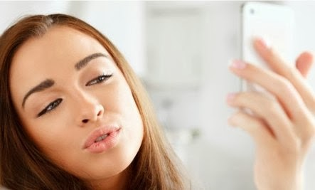 9 Tips To Attract Men Online - girl woman i-phone mobile self-phone smile camera take photo selfshot