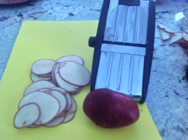 slices of potatoes next to a mandolin slicer