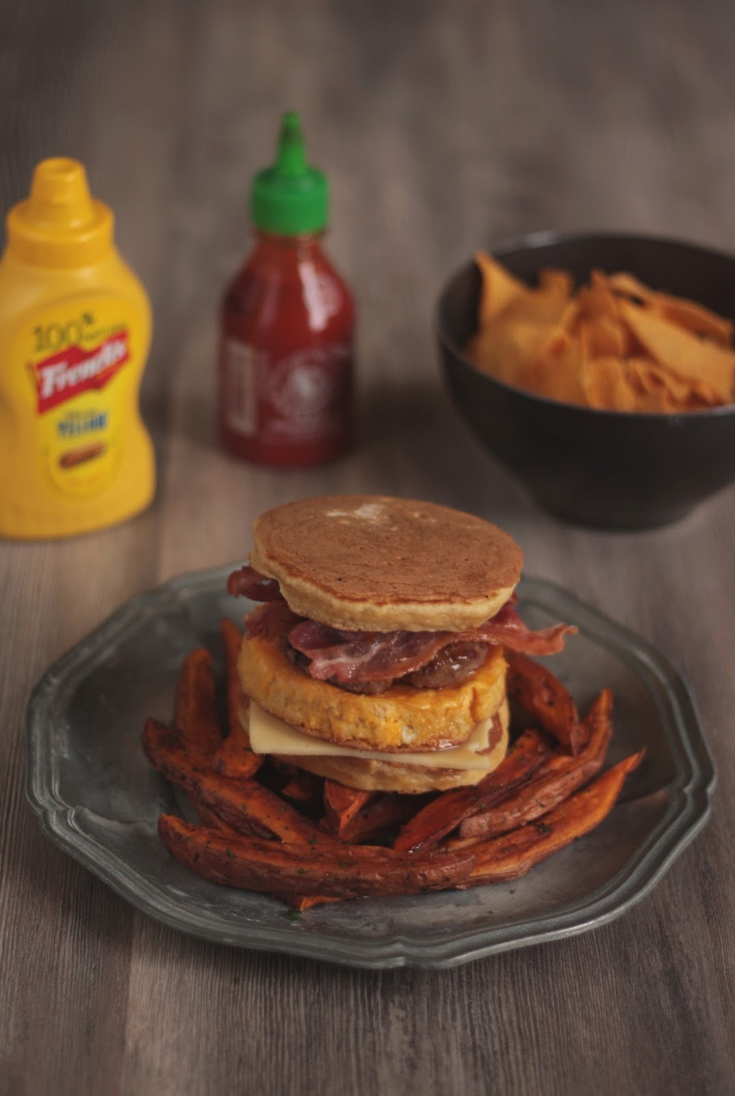 A Texas Pancake Sandwich with Egg and Ground Beef Pattie, Sweet Potato Fries and the best syrup of all times - Sriracha Flavored Maple Syrup - recipe brought to you by Pancake Stories.