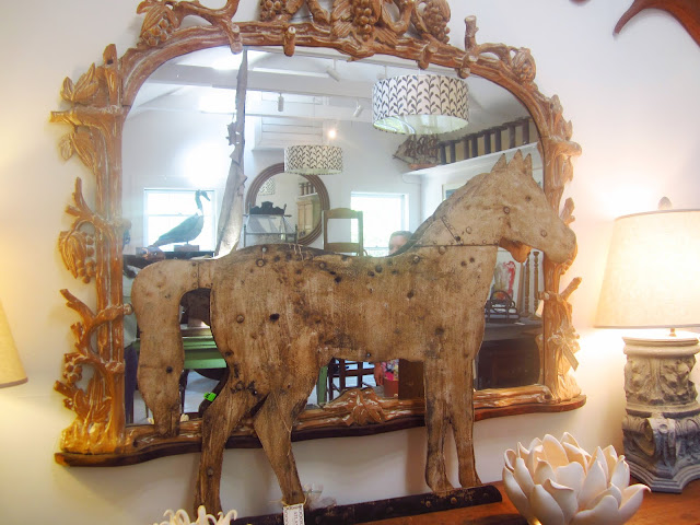 wood horse sculpture on a table leaning up against a large, gold trimmed mirror