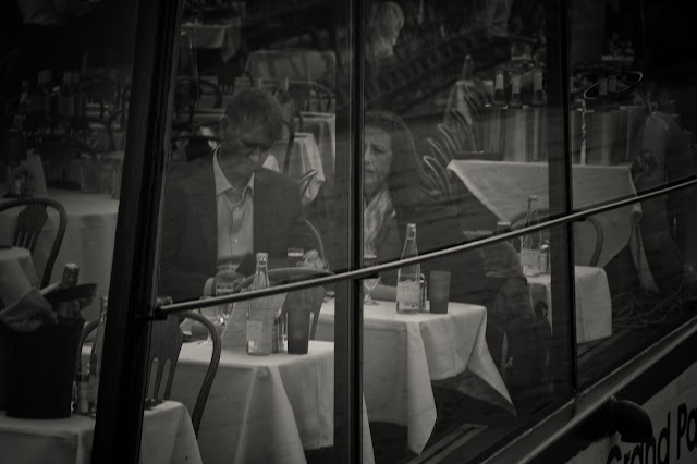 A street photograph of a couple at a table in a French restaurant