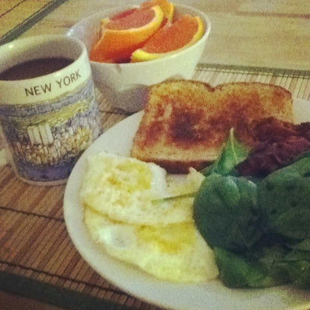 Weekend breakfast: Orange slices, fried eggs, coffee, toast, spinach salad and bacon