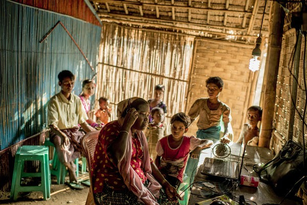 A Rohingya woman at a camp in Sittwe called her brother in Malaysia to ask for money after the burial of their mother. Credit Tomas Munita for The New York ...
