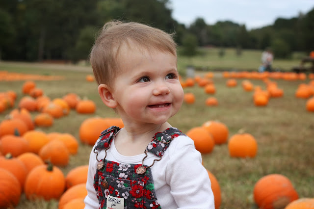 Madeline smiling with pumpkins