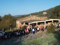 El mas de Sant Pere de les Cigales, amb la cua de marxaires per recollir el primer avituallament, i al fons La Roca