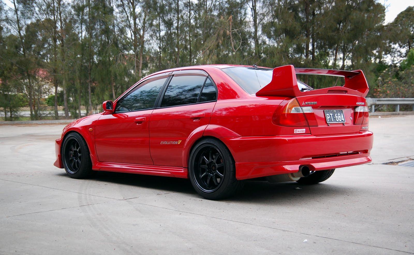 Mitsubishi Lancer Evolution V, kultowa rajdówka z duszą, najlepsze sportowe sedany, 4G63T, AWD, czerwony, czarne felgi, jak wygląda