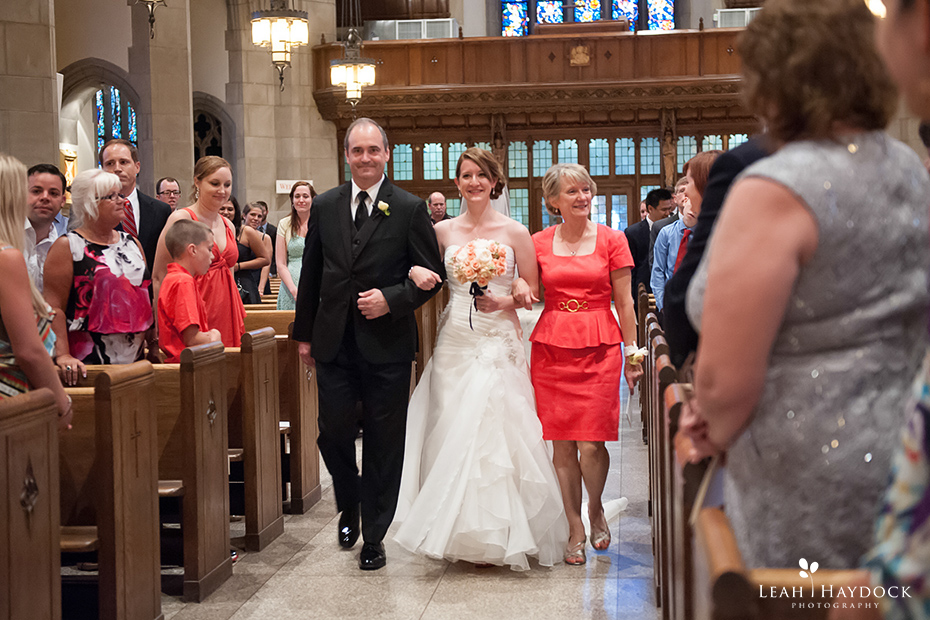 Bride walking down aisle with her parents at St Ignatius Boston