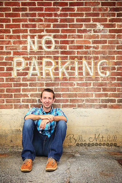senior boy in blue plaid shirt and jeans sitting against brick wall with no parking sign