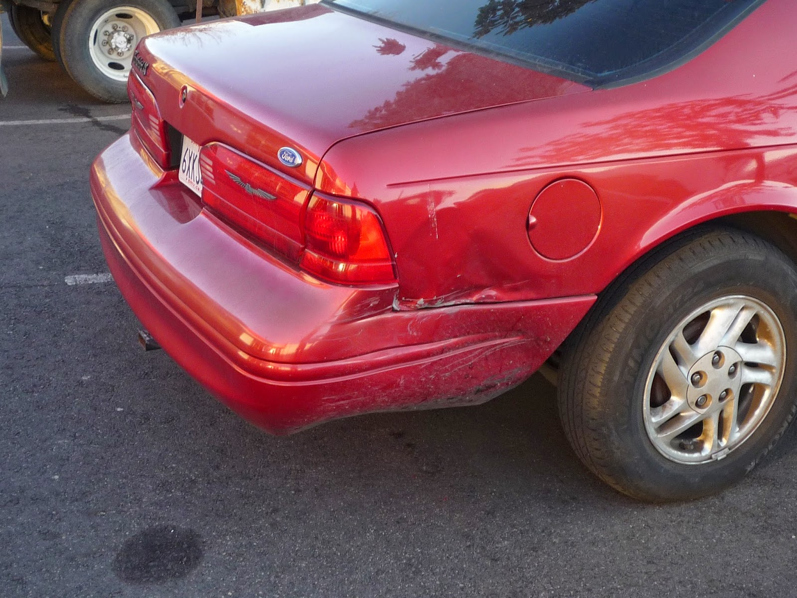 Large dent in bumper and quarter panel on 1996 Ford Thunderbird