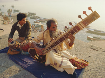 Hindi India playing sitar on the Ganges river shore beach