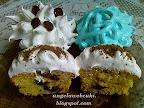Áfonyás muffin fehér csokoládéval, tojáshabbal díszítve, kakaóporral megszórva.