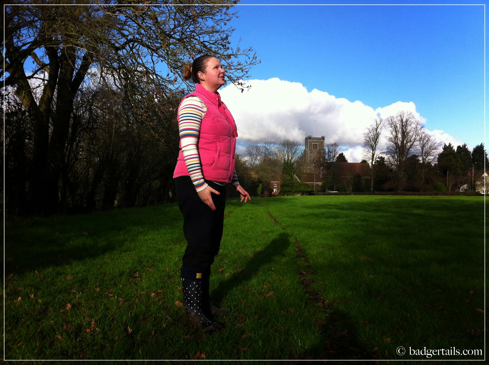 woman stood in english countryside field looking at sky smiling