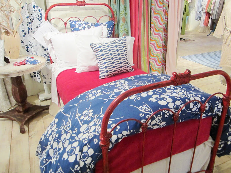 Bed with red iron frame and red, white and blue bedding and pillows