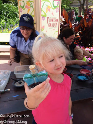 child showing sand art bottle at Epcot Flower and Garden Festival