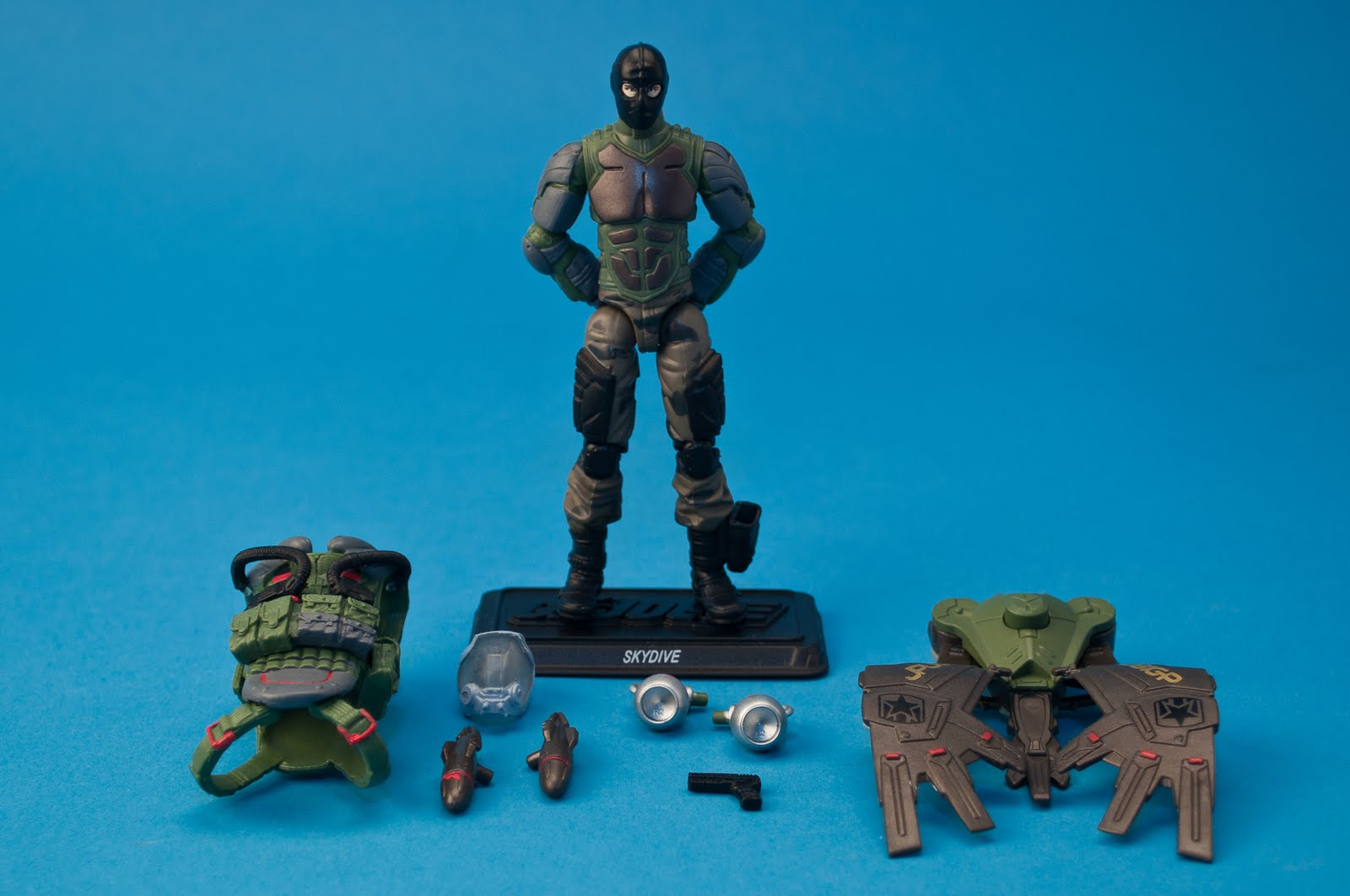 ... helmet, rocket pack with button-activated opening wings, missile (2),  air intake valve (2), pistol, display stand with G.I. Joe logo (SKYDIVE)