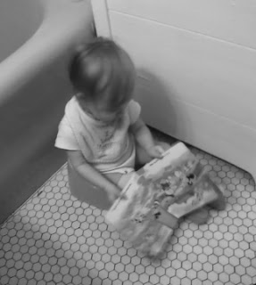 Baby sits on the potty in the bathroom with a book
