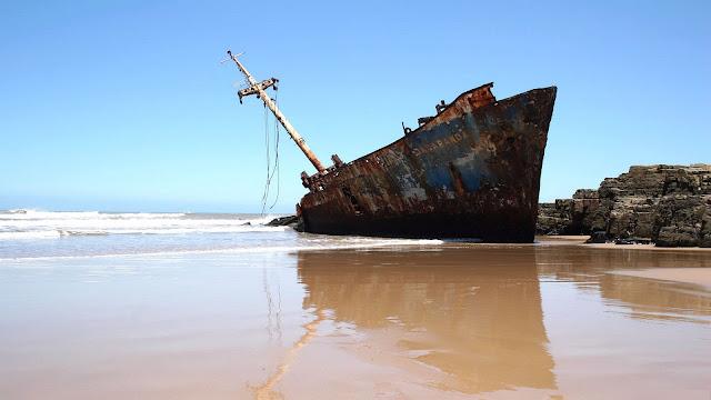 Oud scheepswrak op het strand
