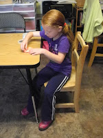 Child sitting crookedly at a table.