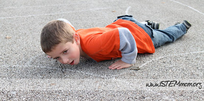 Boy on the ground behaving as a worm in a Worm Game: STEMmom.org