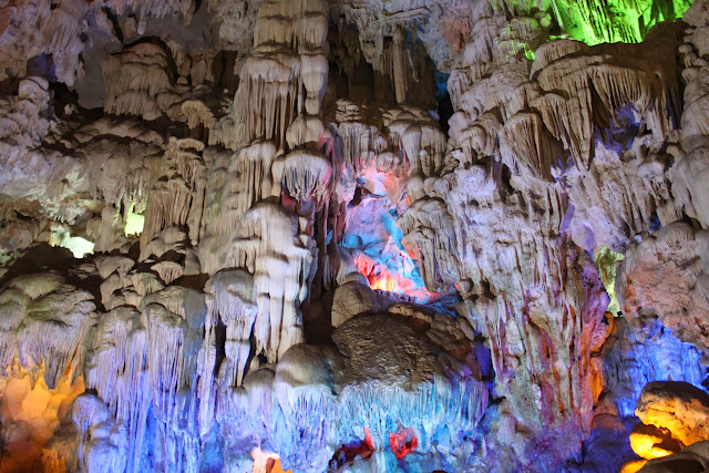 Blue lights flashing on the limestones through the stalactites and stalagmite at Thien Cung Grotto at Halong Bay in Hanoi, Vietnam