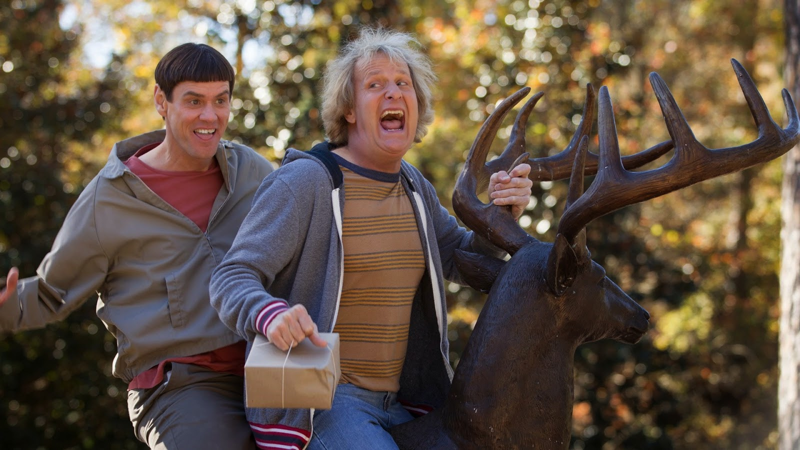Harry and Lloyd riding a deer sculpture in the movie Dumb and Dumber To