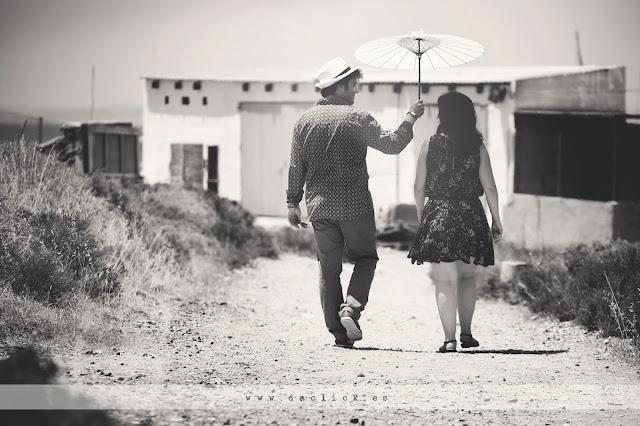 novios de espaldas paseando por tabarca, novio protege del sol a la novia con su sombrilla