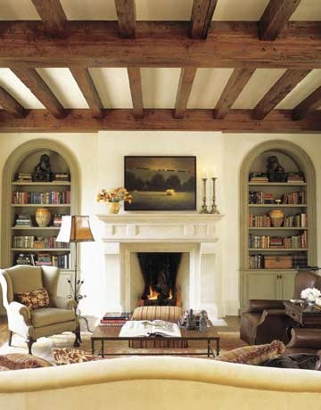 spanish revival living room, stucco fireplace, wood beams, arched windows, spanish eclectic