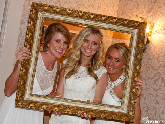 The bride and her bridesmaids pose with a frame in the photo booth area.