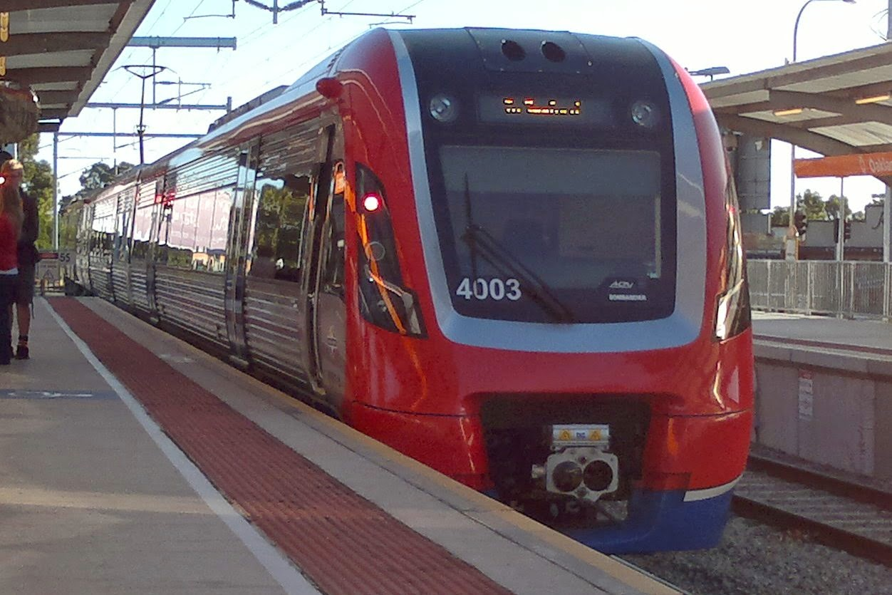 Australian suburban electric passenger train; 4000 class  (no. 4003 entered service circa 2014) ) at a railway station platform. The train has silver sides with a red roof and red ends. Waiting passengers can be seen at the left of the picture.