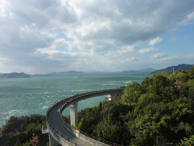 Looping in the sky bridge part of the Shimanami Kaido bikeway as seen from the Kurushima-Kaikyo bridge with the Seto sea and islands in the background
