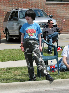 happy vampire, kid, super white, camo pants, by road at parade