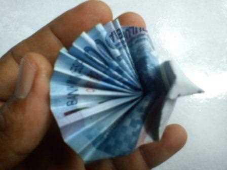 Gambar seni origami melipat uang kertas berbentuk menjadi burung merak cantik unik menarik