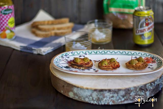 Mini tostas de jamón, queso y aceitunas.