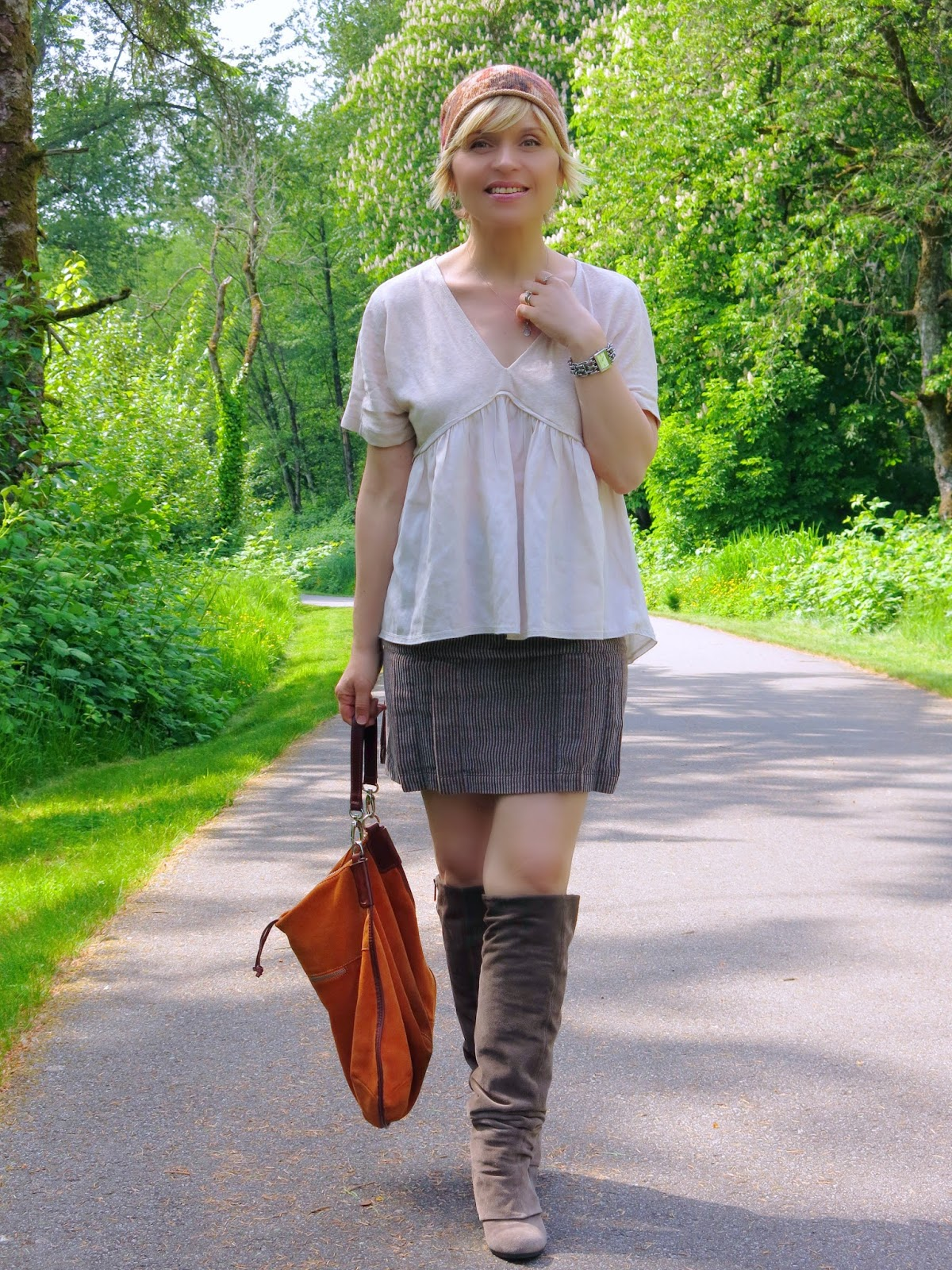 styling a corduroy mini-skirt with suede boots, a Zara top, and a beanie