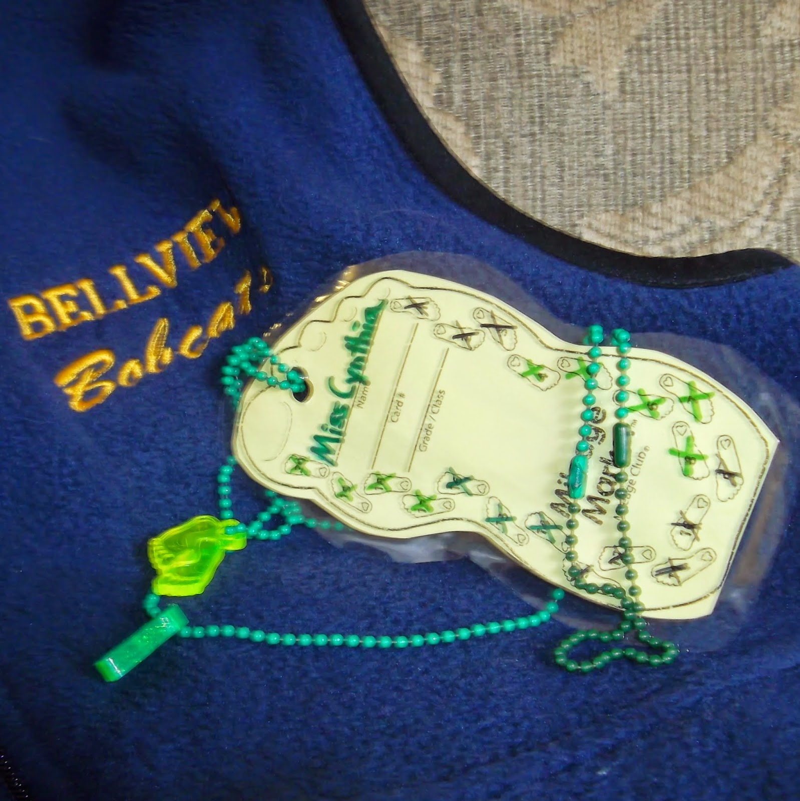 A foot-shaped, laminated card, with Miss Cynthia hand-written on it and X-marks through each of 20 smaller feet that are printed on the card. The laminated card is strung from a green beaded chain with two plastic foot medalions. They lie on a portion of my blue-fleece Bellview Bobcats vest.