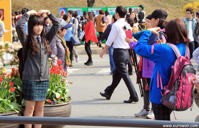 Niña coreana posando haciendo un corazón con los brazos