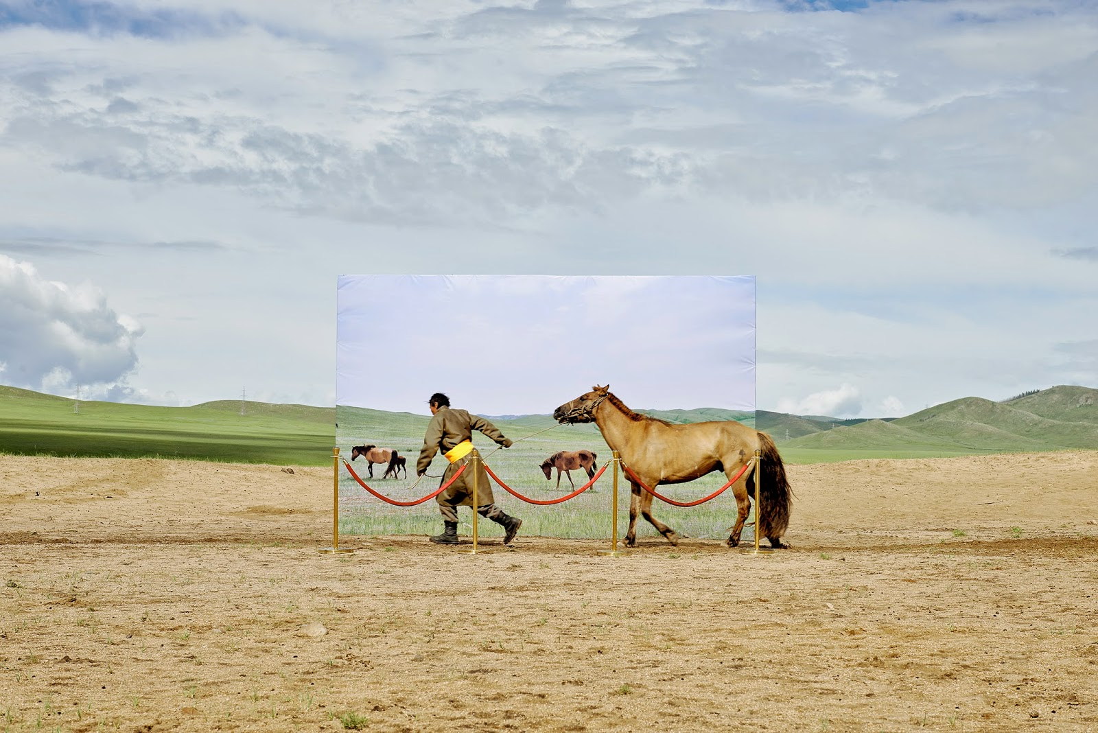 Copyright: ©Daesung Lee, Republic of Korea, Shortlist, Conceptual, Professional Competition, 2015 Sony World Photography Awards. Series Name: Futuristic Archaeology. Series Description: Still 35% of Mongolians are living a nomadic life and depend on their land for survival. This is increasingly difficult due to serious changes: 25% of the Mongolianland has turned into desert in the past 30 years. Potentially 75 % of Mongolian territory is at risk of desertification. These environmental changes directly threaten the Mongolian nomadic way of life, which has been passed from generation to generation. This project attempts at recreating the museum diorama with actual people and their livestock in a real place where decertifying in Mongolia. It is based on an imagination that these people try to go into museum diorama for survival in the future. This is accomplished with printed images on a billboard placed in conjunction with the actual landscape horizon. I hope to accomplish a sense that the lives of these nomadic people occur between this reality and a virtual space of a museum. Mongolian traditional nomadic lifestyle might be existed only in museum in the future.