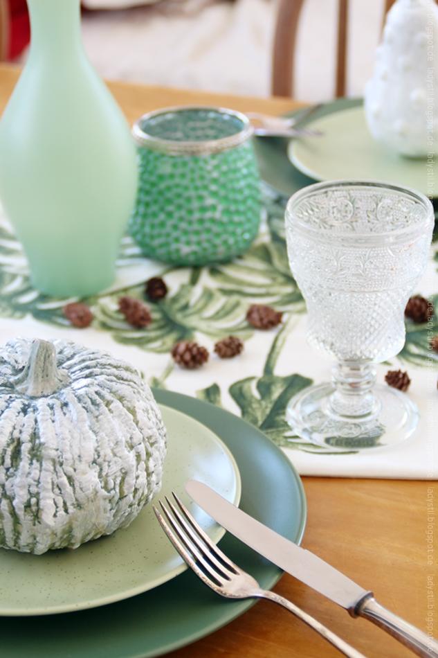 Herbstliche Tischdeko mit grüner Kürbisdekoration und kleinen Tannenzapfen sowie grüner Vase und Windlicht