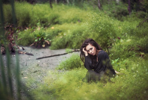 девушка в черном платье сидит на траве